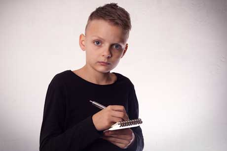 Junge mit Rechenschwäche schaut verängstigt und schreibt in Notizblock