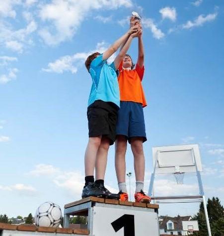 Kinder mit Pokal bei Wettbwerb auf dem Siegertreppchen
