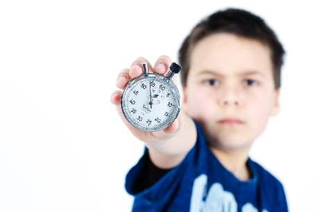 Junge blickt ernst und zeigt eine Stoppuhr wegen Eile und Zeitdruck und Hetze