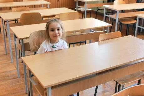 Eine Schülerin sitzt in einem leeren Klassenzimmer