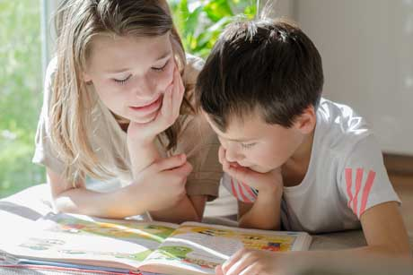 Ein Mädchen und ein Junge lesen gemeinsam ein Buch - jahrgangsübergreifendes Lernen