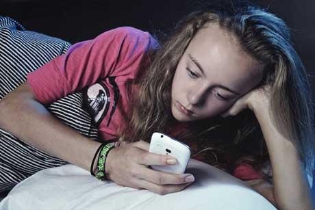 Kind mit Smartphone Handy im Bett