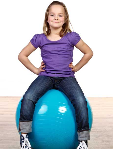 Ein Mädchen sitzt auf einem Gymnastikball Sitzball