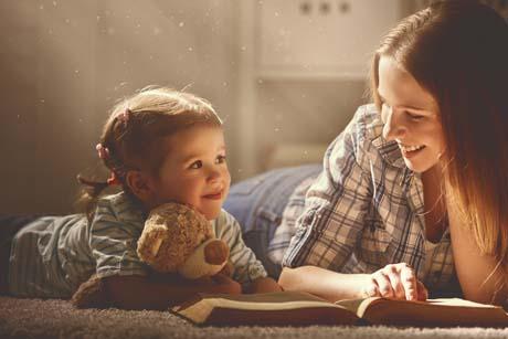 Erziehungsratgeber stellen Eltern-Kind-Beziehung ins Zentrum:Mutter und Tochter beim Buch vorlesen und lächeln