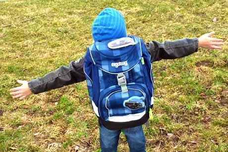 Junge glücklich mit ergobag-Schulranzen Schulrucksack auf seinem Rücken