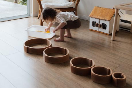 Montessorimaterial Ein Kind spielt versonnen mit Ringen aus Holz und schüttet