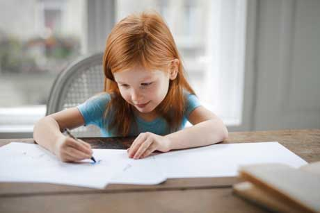 Kleines Mädchen lernt fleißig und füllt Arbeitsblätter nach Montessori-Pädagogik aus